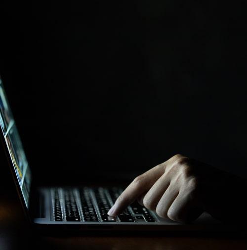 hand-man-using-laptop-computer-dark (1)-1
